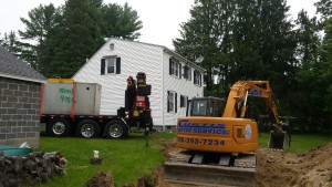 Dropping in the septic tank into place.